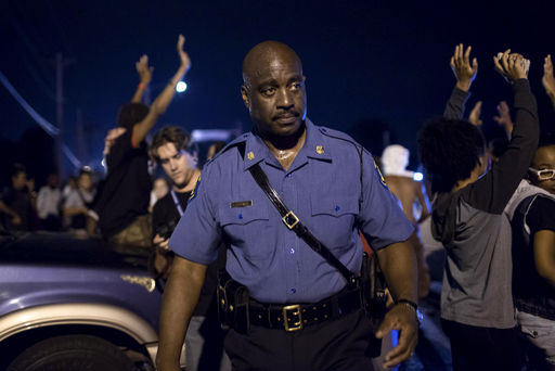 Capt. Ron Johnson of the Missouri State Highway Patrol walks through a crowd of demonstrators along West Florissant Avenue in Ferguson, Mo.